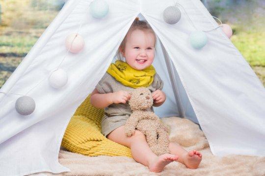 zdjęcie dziecka siedzącego w namiocie tipi